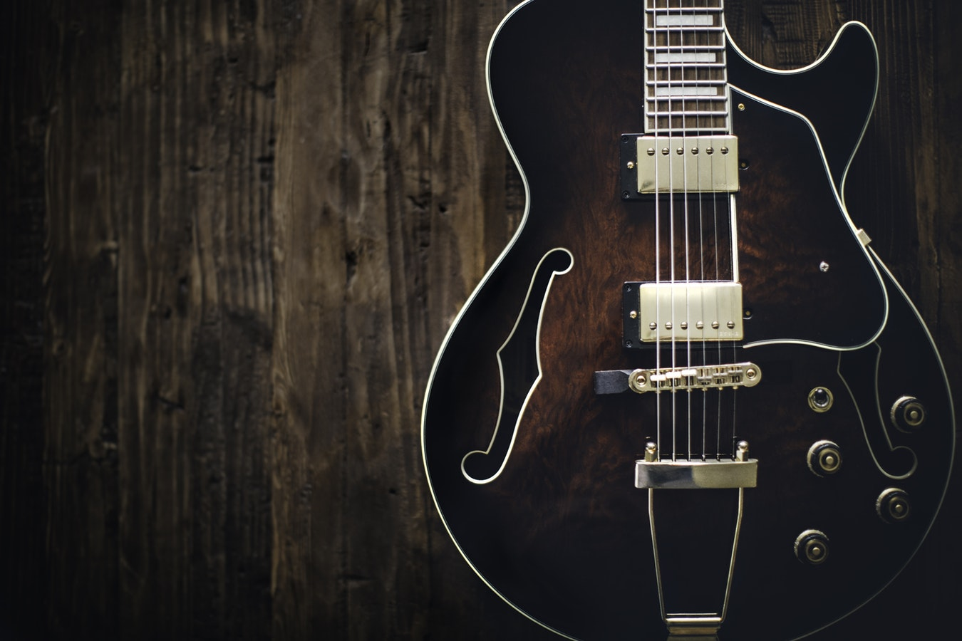 dark wood colored guitar leaning on wall