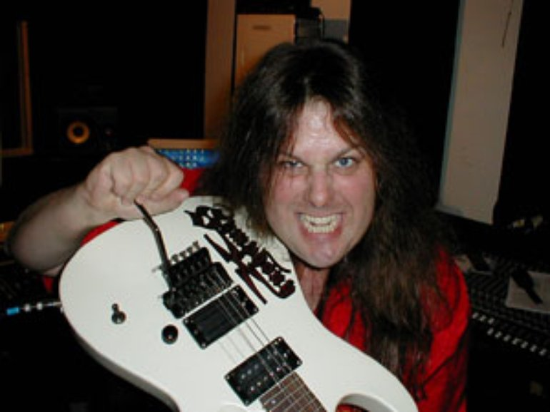 Michael Romeo holding guitar looking crazy